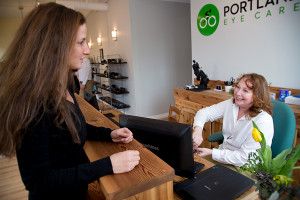 optician helping patient with prescription from Portland optometrist